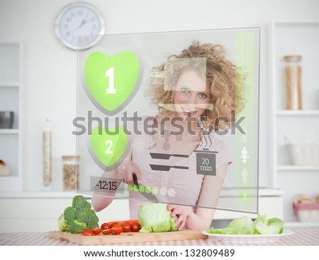 Smiling woman making salad using hologram interface in the kitchen - stock photo