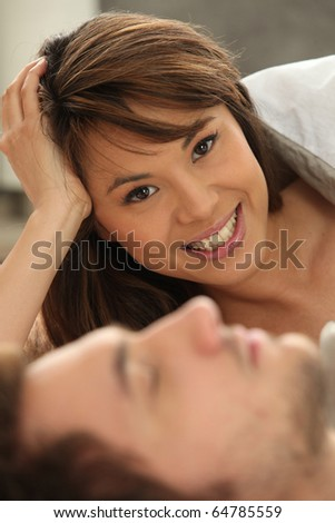 Smiling woman next to a sleeping man