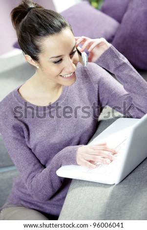 Smiling Woman on Couch With Laptop and Cell Phone