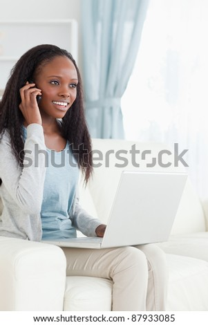 Smiling woman on her phone while using laptop