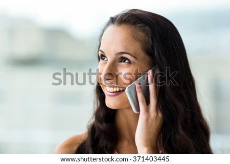 Smiling woman on phone call next to window - stock photo