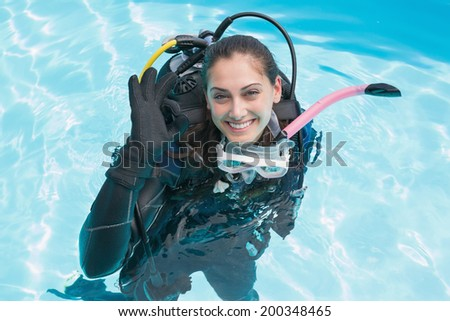 Smiling woman on scuba training in swimming pool making ok sign on a sunny day - stock photo