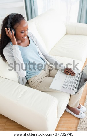Smiling woman on sofa listening to music and using her laptop