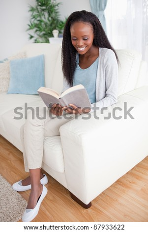 Smiling woman on sofa reading a book