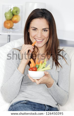smiling woman on sofa with vegetable salad - stock photo