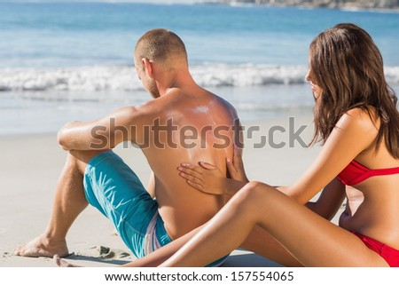 Smiling woman on the beach putting sun cream on her boyfriends back - stock photo