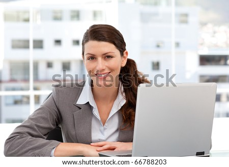 Smiling woman on the computer looking at the camera in her office - stock photo