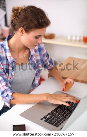 Smiling woman online shopping using computer and credit card in kitchen - stock photo