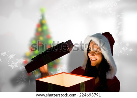 Smiling woman opening christmas present against blurry christmas tree in room - stock photo