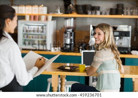Smiling woman ordering coffee from waitress in cafe