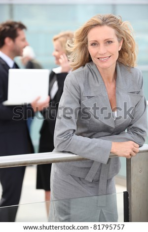 Smiling woman outside office building - stock photo