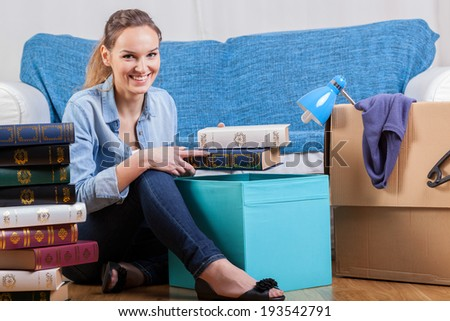 Smiling woman packing books during moving house - stock photo