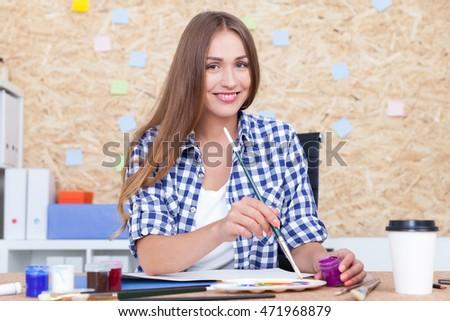 Smiling woman painter looking to camera mixing paint and drawing. Paper coffee cup on table. Concept of creative work