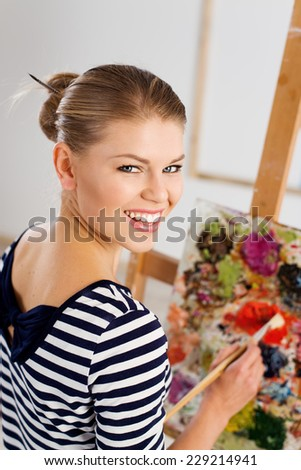 Smiling woman painter with paintbrush standing at easel drawing with acrylic paints. Young pretty girl working in her artistic studio.  - stock photo