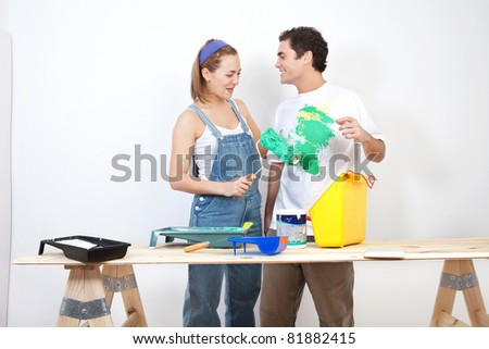 Smiling woman painting husband's t-shirt with roller - stock photo