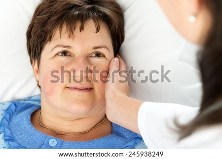Smiling woman patient lying in bed - stock photo