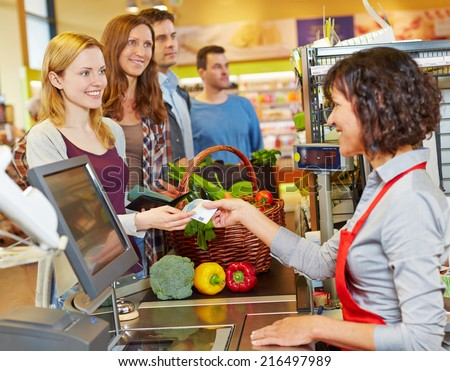 Smiling woman paying cash with Euro money bill at supermarket checkout - stock photo