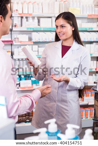 Smiling woman pharmacist counseling customer about drugs usage in modern farmacy