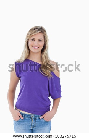 Smiling woman placing her hands in her pockets against a white background