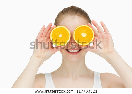 Smiling woman placing oranges on her eyes against white bakground
