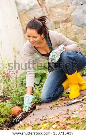 Smiling woman planting gardening flowerbed autumn hobby housework - stock photo
