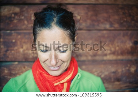 Smiling woman portrait with wood wall as background.