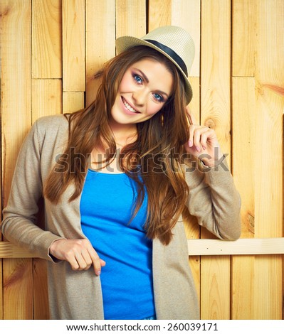 Smiling woman portrait with yellow hat. Young model with long hair standing against wooden wall. - stock photo