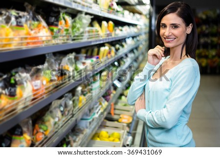 Smiling woman posing for camera in supermarket - stock photo