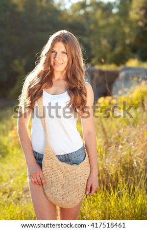 Smiling woman posing outdoors. Looking at camera. Wearing summer casual clothes. 20s. - stock photo