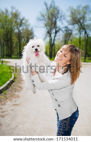 Smiling woman posing with a white dog in the park