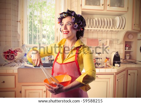 Smiling woman preparing food in a kitchen - stock photo