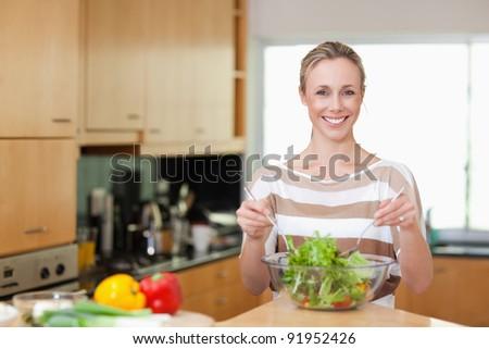 Smiling woman preparing healthy salad - stock photo