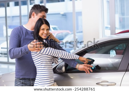 Smiling woman presenting her new car at new car showroom - stock photo