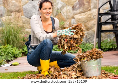 Smiling woman putting leaves in bucket fall garden housework - stock photo