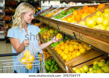 Smiling woman putting oranges in plastic bag at grocery shop - stock photo