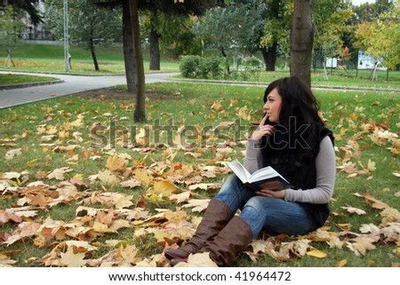 Smiling woman reading a book in autumn park