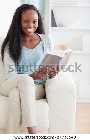 Smiling woman reading a book on couch