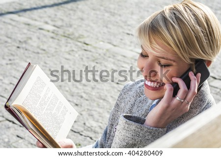 Smiling woman reading a book outdoors