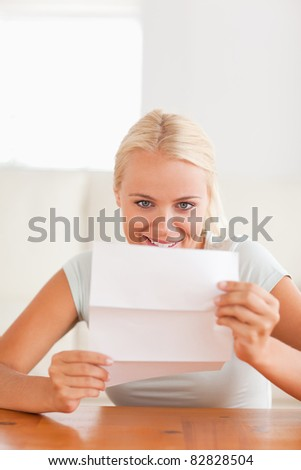Smiling woman reading a letter in her living room - stock photo