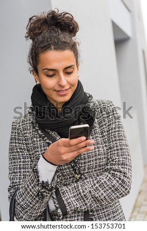 Smiling woman reading text message on her smartphone in coat - stock photo