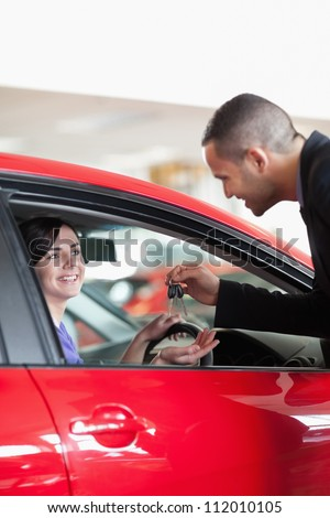 Smiling woman receiving car keys while sitting on a car