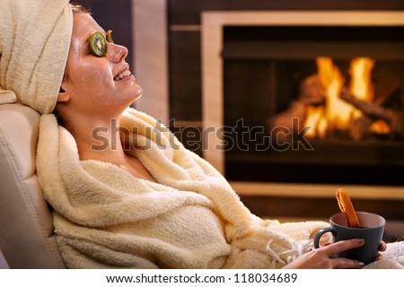 Smiling woman relaxing at home with kiwifruit facial mask and tea mug, sitting in bathrobe in front of fireplace. - stock photo
