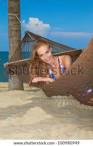 Smiling woman relaxing in a hammock on a sandy beach enjoying an idyllic tropical getaway - stock photo