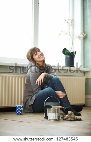 Smiling woman renovating and relaxing at home - stock photo