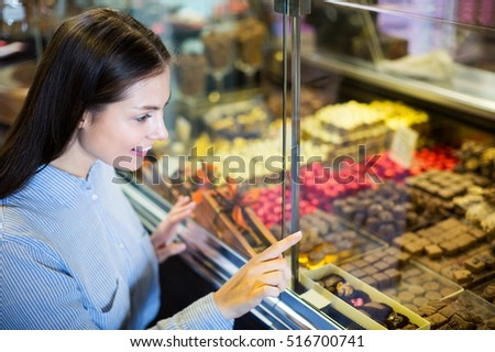 Smiling woman selecting fine chocolates and confectionery at cafe display