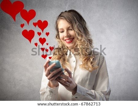 Smiling woman sending love sms with a mobile phone - stock photo