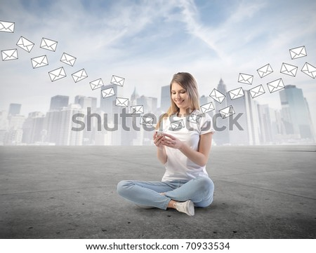 Smiling woman sending sms from a mobile phone with cityscape on the background - stock photo