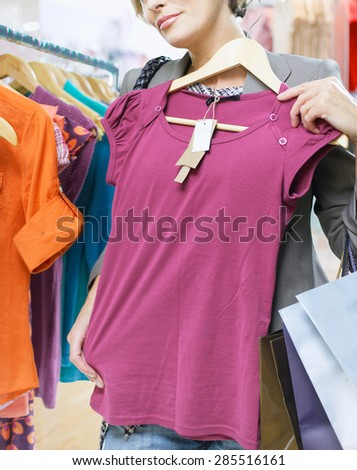 smiling woman shopping in retail store - stock photo