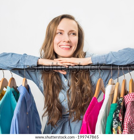Smiling woman shopping in retail store over light grey background - stock photo