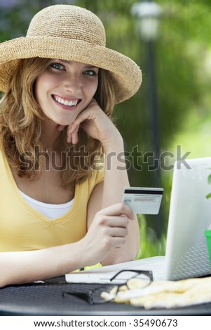 Smiling woman shopping on-line with credit card and laptop outside - stock photo